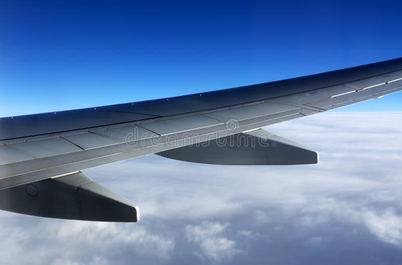 Крыло самолета над облаками стоковая фотография