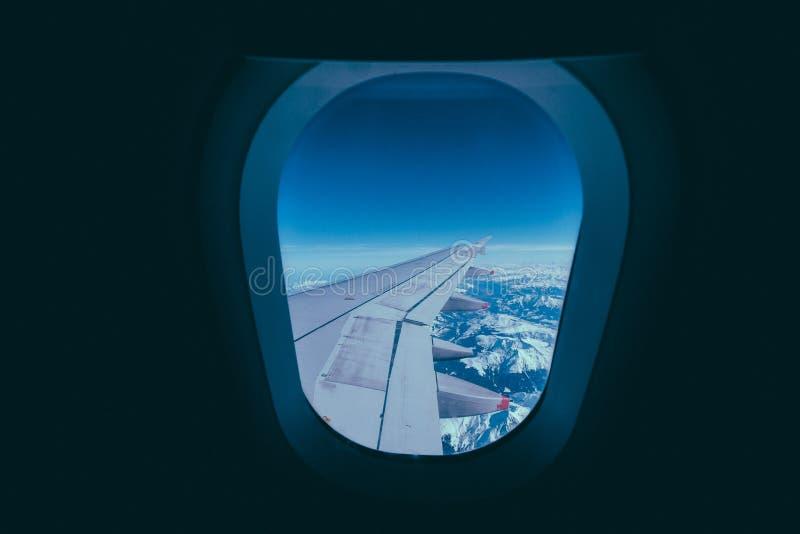 Крыло самолета над снежными горами снятыми из окна стоковые изображения
