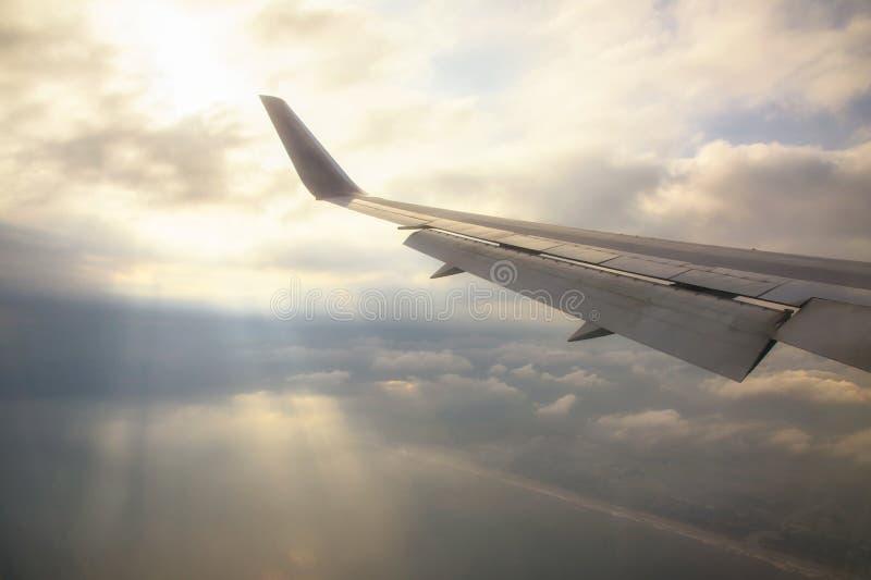 Крыло самолета с лучами через облака стоковые фотографии rf