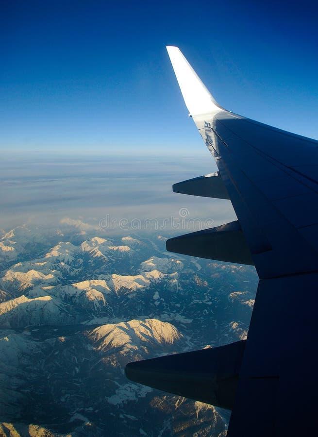 Крыло самолета с снегом покрыло горы в предпосылке стоковые фотографии rf