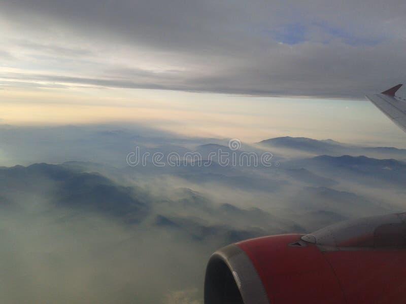 Крыло самолетного двигателя с сногсшибательными горами и предпосылкой неба стоковые фото