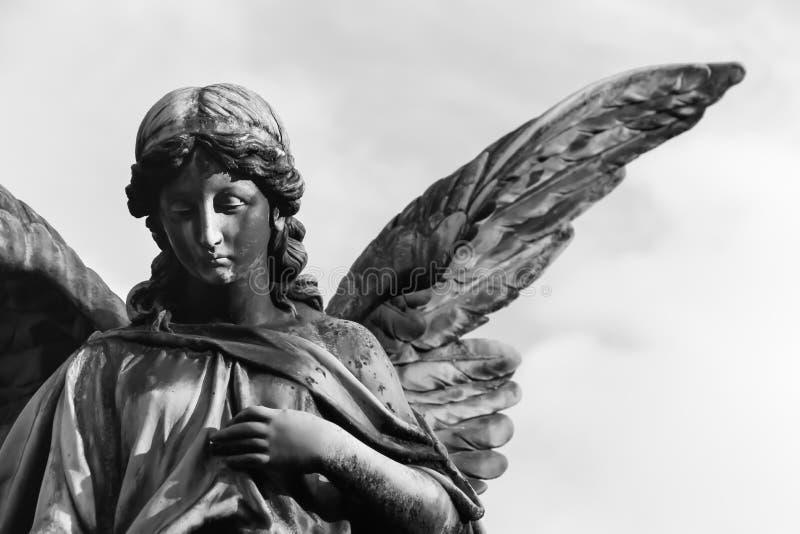 Крылья грустной скульптуры ангел-хранителя открытые длинные через рамку против яркого белого неба Грустная скульптура выражения с стоковые фотографии rf