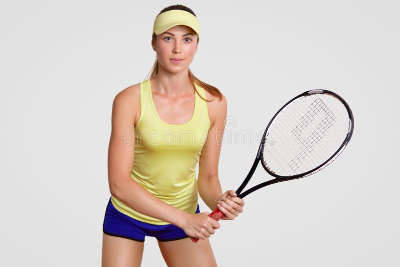 Крытая съемка активного красивого женского теннисиста стоит в готовой позиции, теннисе игр, подготавливает для того чтобы пнуть ш стоковые фотографии rf