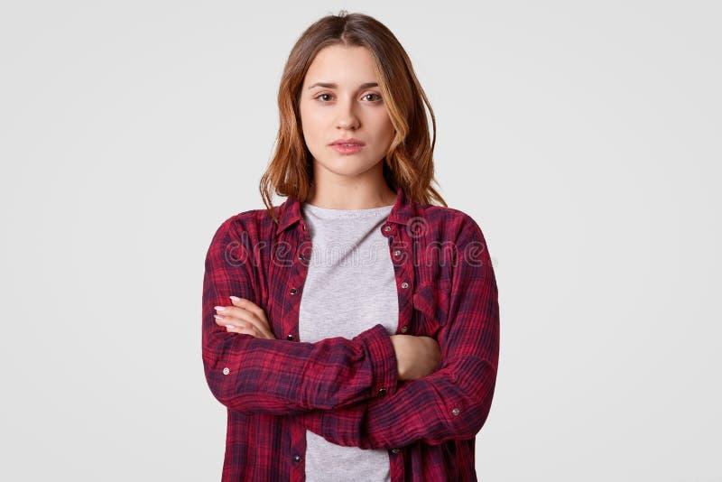 Крытая съемка девочка-подростка серьезной собственной личности уверенного держит руки пересеченный, носит checkered рубашку, смот стоковые изображения