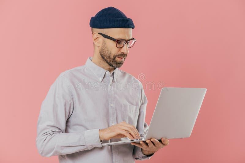 Крытая съемка занятого мужского фрилансера носит оптически стекла для хорошего зрения, держит современное электронное устройство, стоковое фото rf