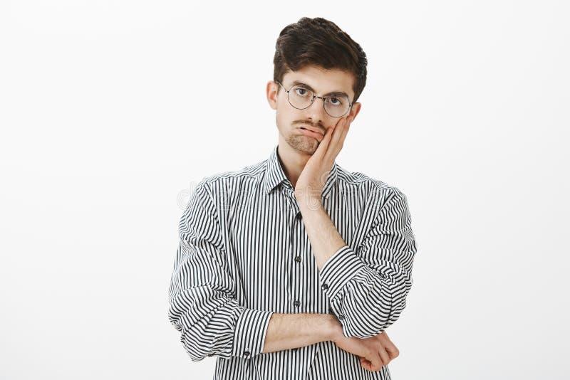 Крытая съемка поданной вверх пробуренной зрелой мужской модели в striped рубашке, держа ладонь на щеке и дышая вне, вытаращить на стоковая фотография rf