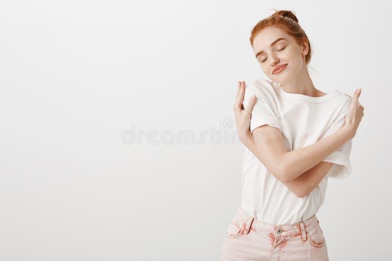 Крытая съемка романтичной и чувственной европейской женщины с волосами имбиря в стильном обмундировании, обнимающ нежно, усмехаяс стоковые изображения rf