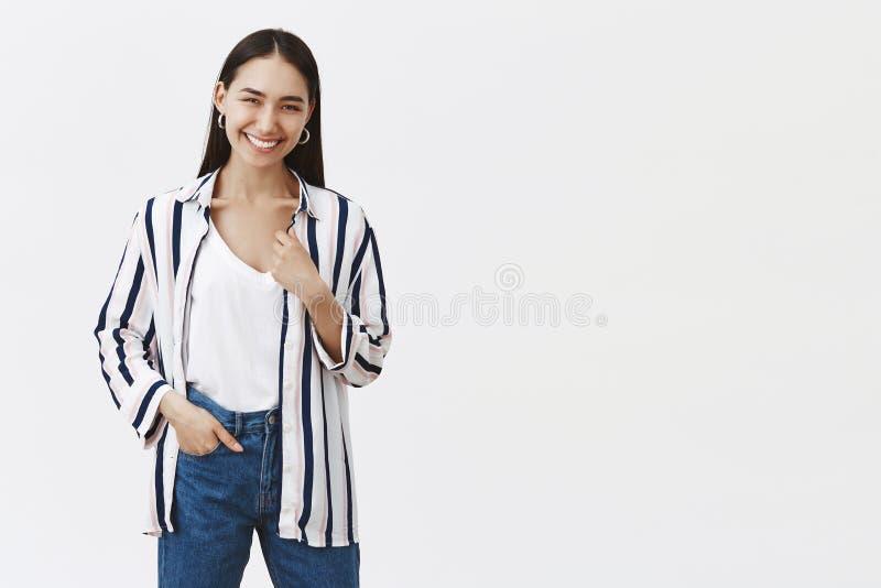 Крытая съемка счастливого успешного молодого женского предпринимателя в striped блузке и джинсах, держащ руку в карманн, усмехаяс стоковая фотография
