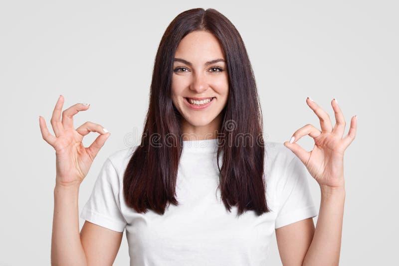 Крытая съемка счастливой привлекательной женщины с длиной прямыми темными волосами, делает одобренный знак с обеими руками, показ стоковые фотографии rf