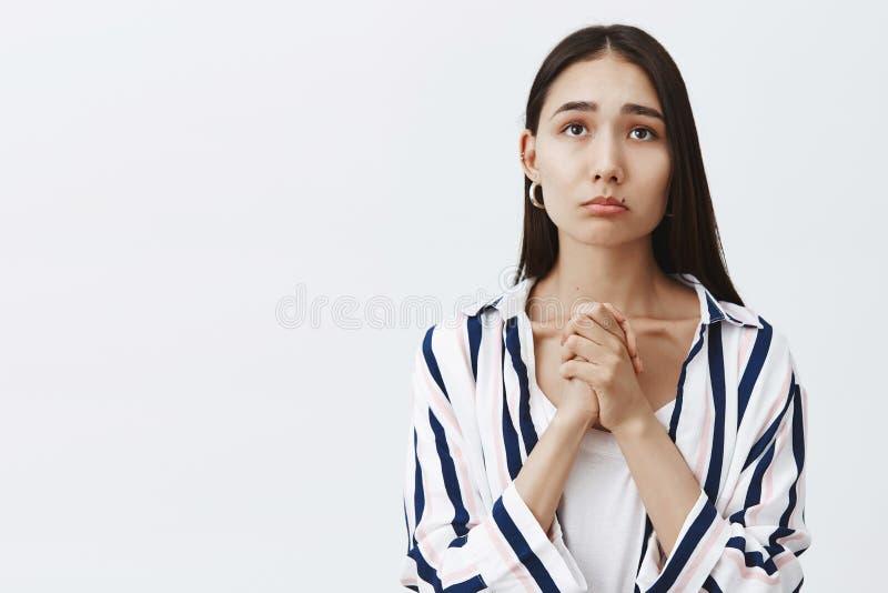 Крытая съемка хмурой милой женщины в striped блузке над футболкой, сжимая руки и морща губы, хмурясь пока gazing стоковое изображение