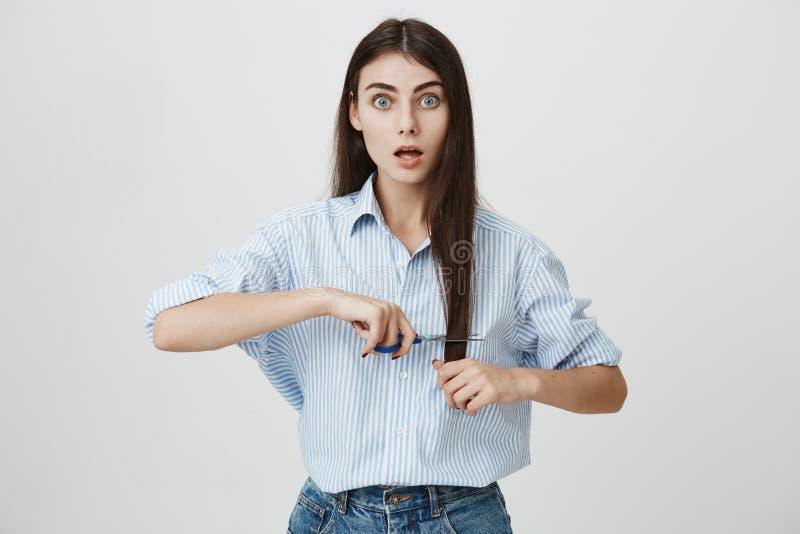 Крытый портрет изумленного и сотрясенного милого европейского женского вырезывания ее волосы с ножницами пока стоящ над серым цве стоковая фотография rf