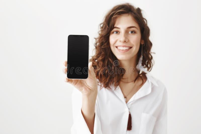 Крытый портрет очаровательной молодой женщины с вьющиеся волосы усмехаясь обширно пока держащ smartphone, рекламируя устройство стоковые фотографии rf