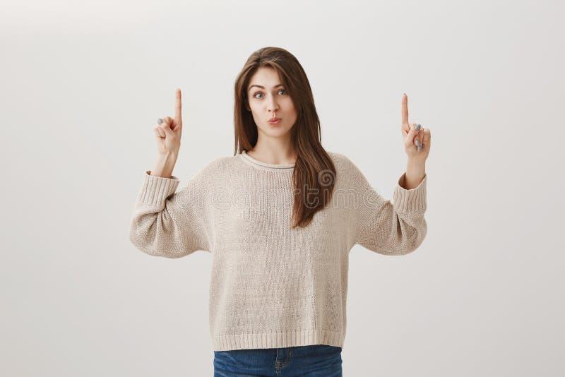 Крытый портрет очаровывая девушки вида европейской с волосами брюнета поднимая указательные пальцы и указывая вверх, puckering гу стоковые фотографии rf