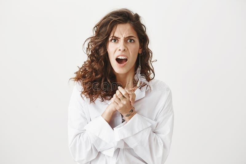 Крытый портрет сумашедшей выразительной женщины крича и хмурясь пока сжимающ вручает около комода, стоя против серого цвета стоковое изображение rf