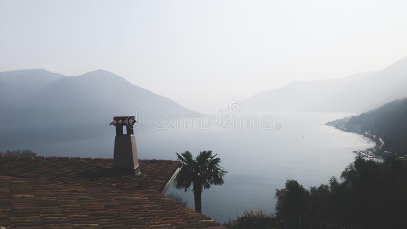 Крыть черепицей черепицей верхняя часть и пальмы крыши обозревая мглистые горы и озеро стоковое изображение