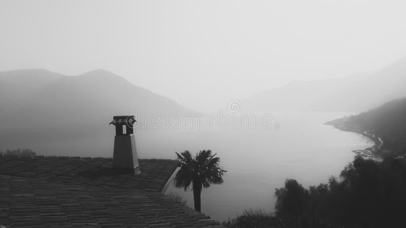 Крыть черепицей черепицей верхняя часть и пальмы крыши обозревая мглистые горы и озеро стоковое фото