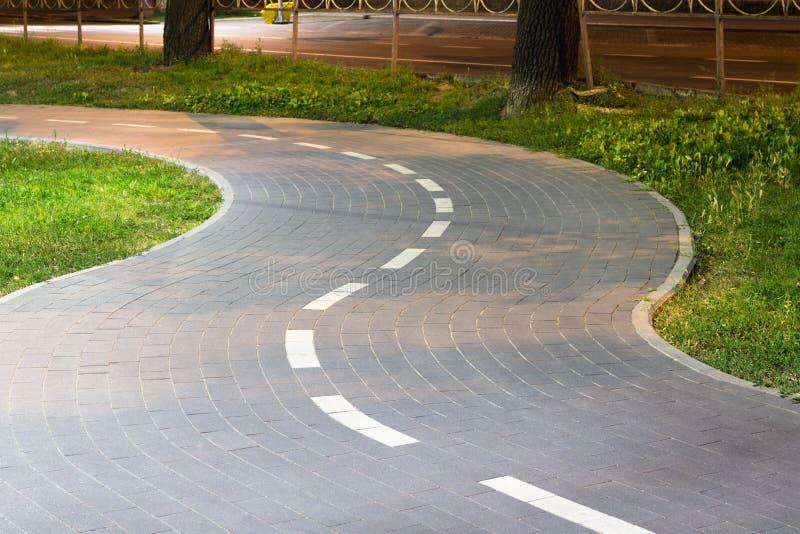 Крыть черепицей черепицей путь велосипеда Изгибать тротуар Извилистая дорога стоковые фотографии rf