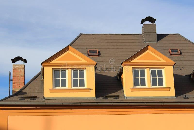 Крыша большого дома города с 2 печными трубами кирпичей с крышками металла и 2 люками крыши и 2 dormers в неоклассическом остросл стоковые изображения