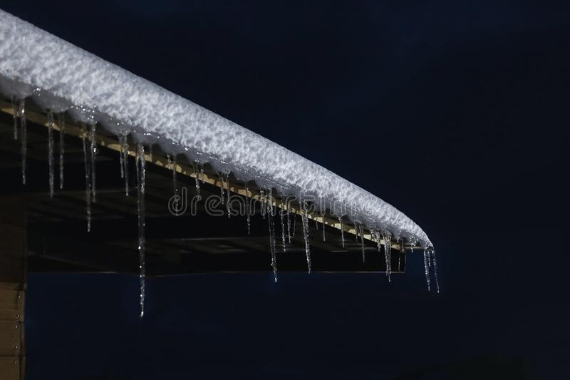Крыша дома со снегом и сосульками вечером стоковая фотография rf