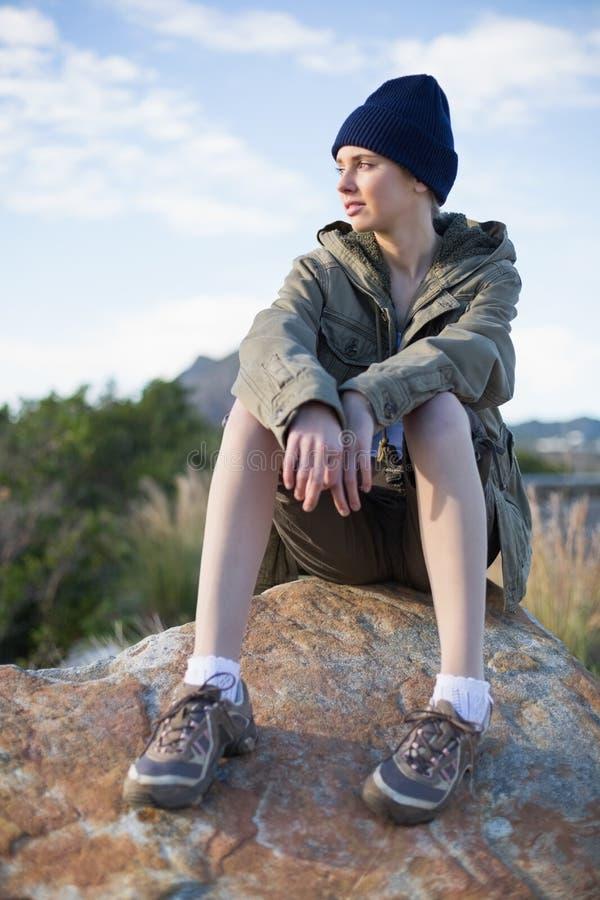 Download Крышка женщины нося сидя на утесе Стоковое Фото - изображение насчитывающей bootless, фронт: 33739470