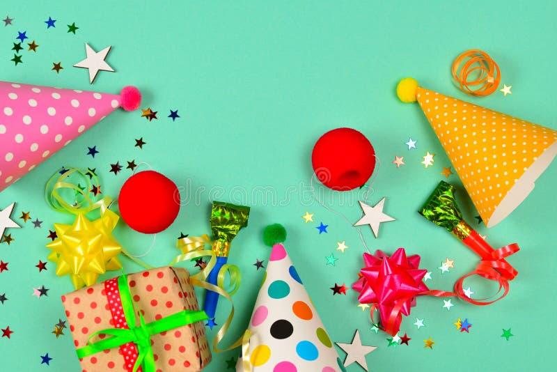 Крышки дня рождения, настоящий момент, confetti, ленты, звезды, носы клоуна на зеленой предпосылке Космос для текста или дизайна стоковые фотографии rf