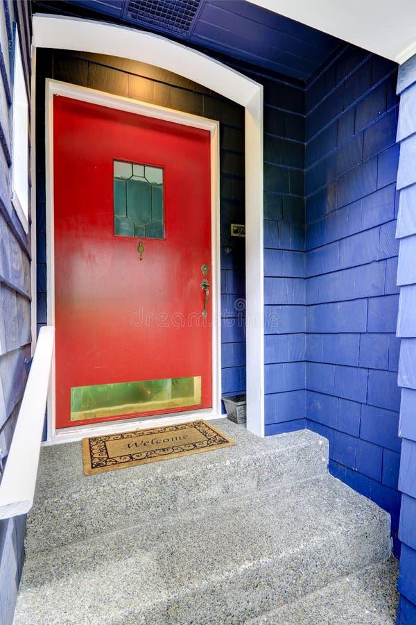 Крылечко входа с яркой красной дверью стоковая фотография