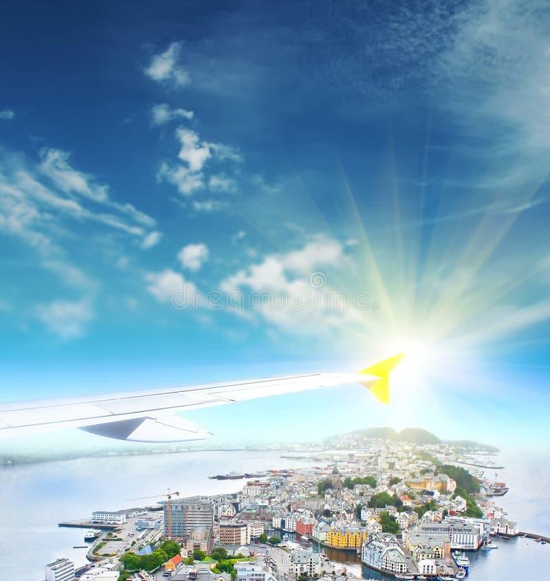 Крыло летания самолета над городом на восходе солнца стоковые фото