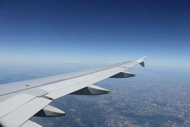 Крыло самолета летая над землей стоковое изображение