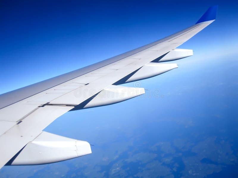 Крыло самолета на предпосылке голубого неба изолированная иллюстрация глобуса принципиальной схемы предпосылки самолета surranded стоковые фото