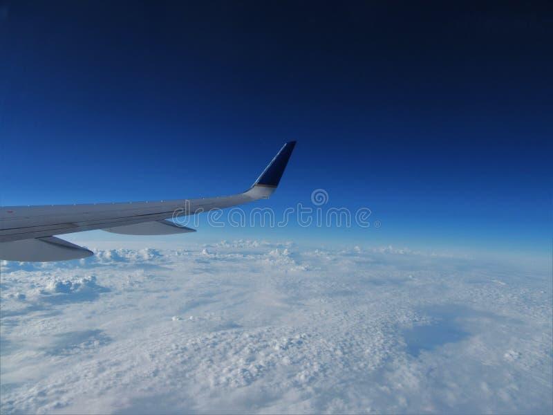 Крыло самолета пассажирского самолета летая над толстой грядой облаков стоковая фотография