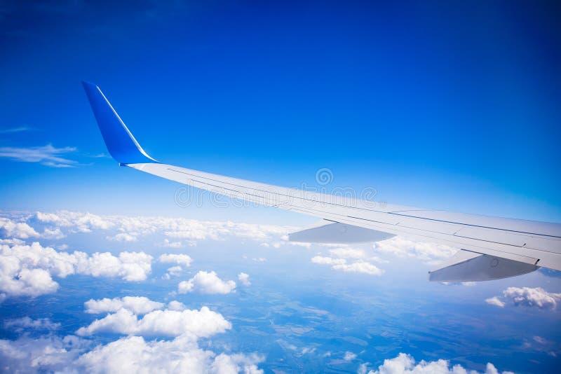 Крыло самолета с голубым небом и белыми облаками стоковые изображения rf