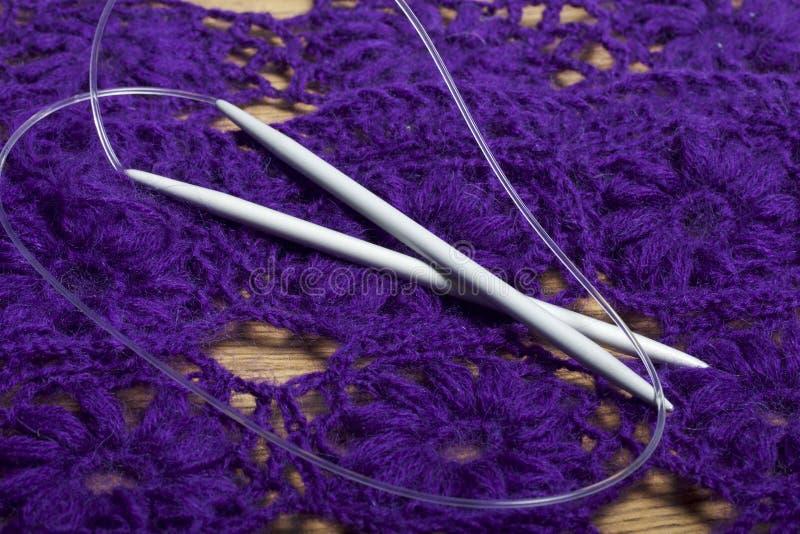 Крюки для вязать на фоне связанного фиолетового портмона стоковое фото