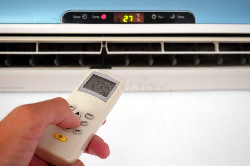 Кто-то изменяя установки отечественных AC или воздуха Conditioni стоковая фотография rf