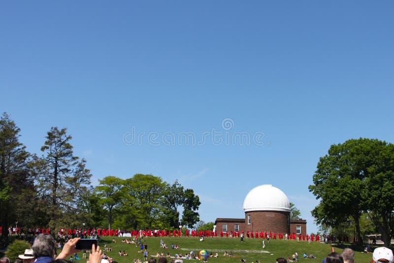 Кто-то принимает фото телефона студент-выпускников храня перед обсерваторией на градации Middletown Коннектикуте США веслианского стоковое изображение rf