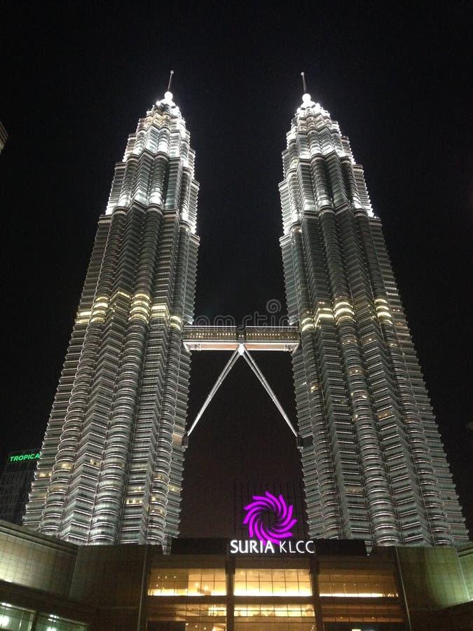 Куала-Лумпур, Малайзия - 22-ое апреля 2017: Взгляд ночи загоренных Башен Близнецы Petronas и моста в Куалае-Лумпур, Малайзии стоковое изображение