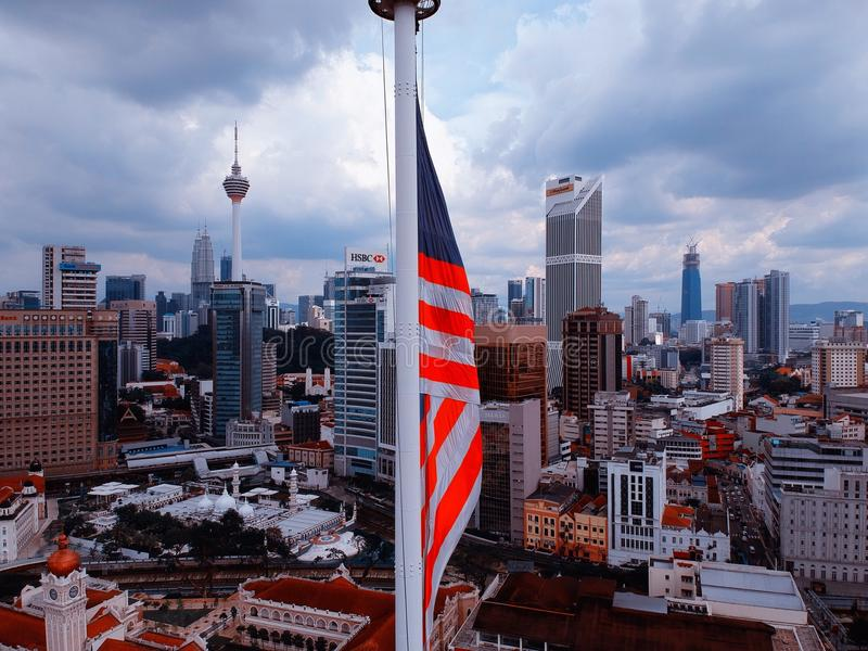 Куала-Лумпур, Малайзия - 28-ое декабря 2017: Вид с воздуха флага ` s Малайзии с предпосылкой горизонта города Куалаа-Лумпур стоковое изображение