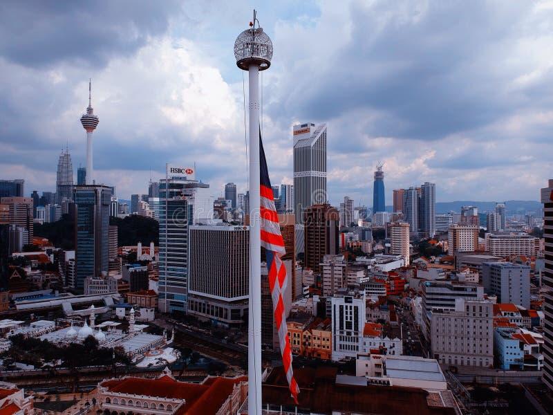 Куала-Лумпур, Малайзия - 28-ое декабря 2017: Вид с воздуха флага ` s Малайзии с ubackgr горизонта города Kuala Lumpuor стоковые изображения