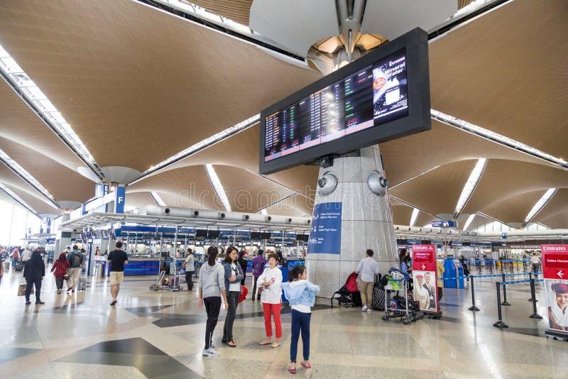 КУАЛА-ЛУМПУР, МАЛАЙЗИЯ, 3-ье ноября 2018: Путешественники идя вокруг определять их счетчики регистрации полетов на главном depart стоковая фотография rf