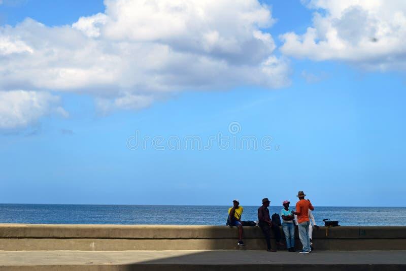 Куба, Гавана, 10-ое февраля 2018: люди принимая перерыв усаженный против seascape в Гаване стоковое фото rf