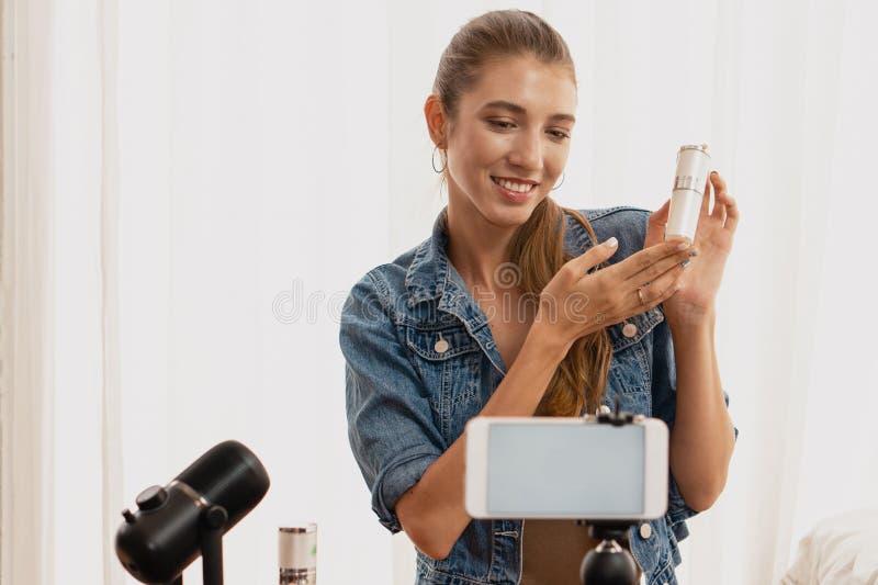 кубинская молодая девушка представляет своим последователям косметические продукты, передавая нам смартфон стоковые изображения rf