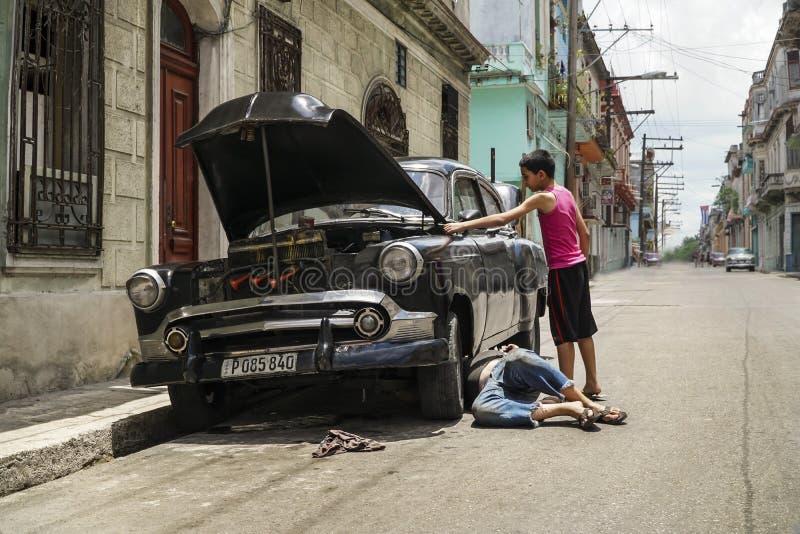 Кубинський человек ремонтируя классический автомобиль на улице в Гаване, Кубе стоковое фото rf