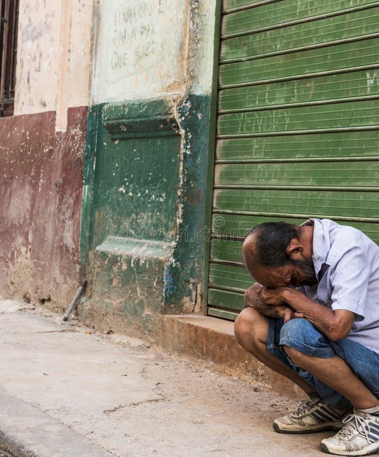 Кубинський человек смотрит в отчаянии сидя на обочине стоковые фото