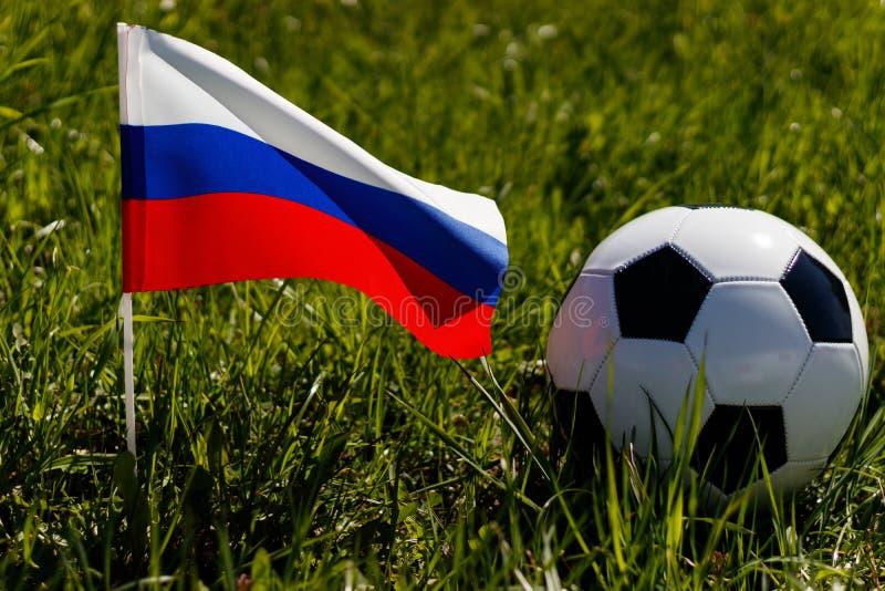 Кубок мира в России Футбольный мяч на траве и русском флаге стоковые фотографии rf