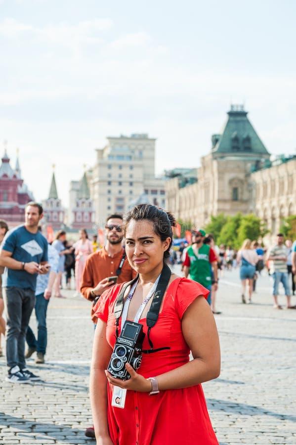 Кубок мира 2018 ФИФА Футбольный болельщик девушки в красном платье с зеркальной камерой Rolleiflex Двойн-объектива на красной пло стоковые изображения rf
