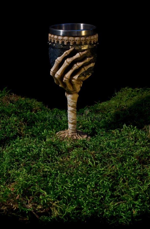Кубок хеллоуина украшенный с каркасными рукой и черепами на передней части стоковое изображение