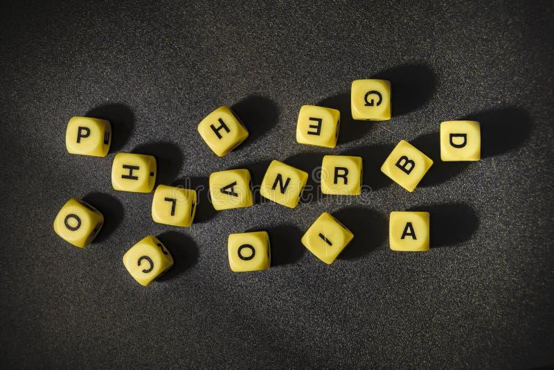 Кубы игры писем над черной предпосылкой стоковая фотография