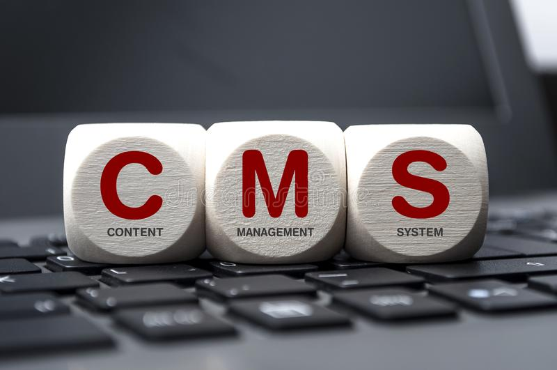 Кубы и кость на клавиатуре ноутбука с системой управления содержания CMS стоковое фото
