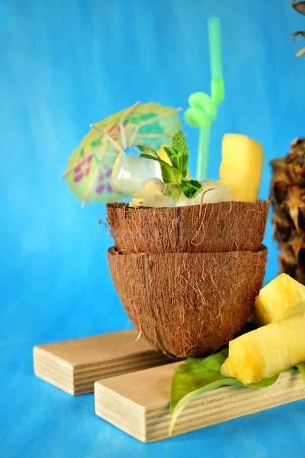 Кубы льда и части ананаса служили в половине кокоса украшенные с зонтиком и соломой на голубой предпосылке стоковые изображения rf