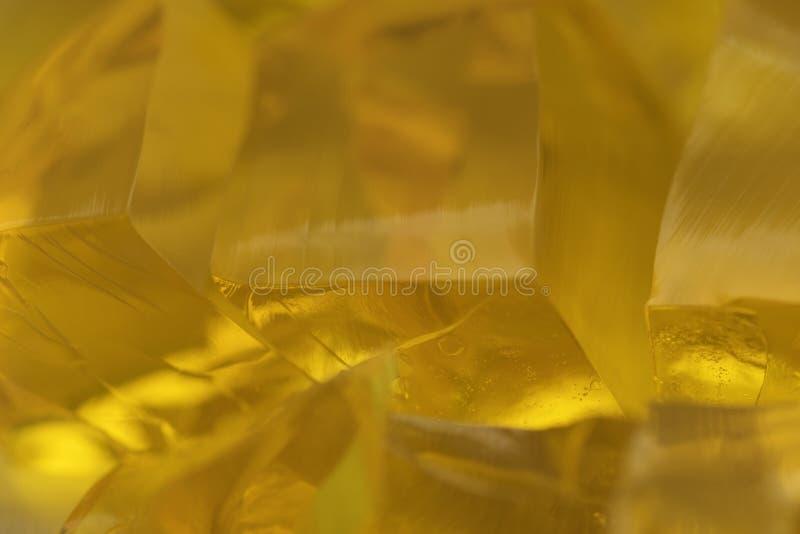 Кубы частей желтого мармелада weet макроса студня золотые сжимают коллаген еды абстрактного свежего десерта сочный стоковое фото