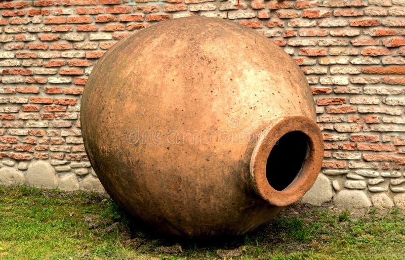 Кувшин †Qvevri «для виноделия на предпосылке кирпичной стены Как амфора стоковое фото
